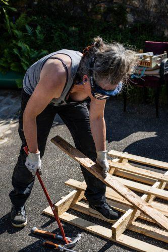 femme entrain de démonter des palettes de récupération